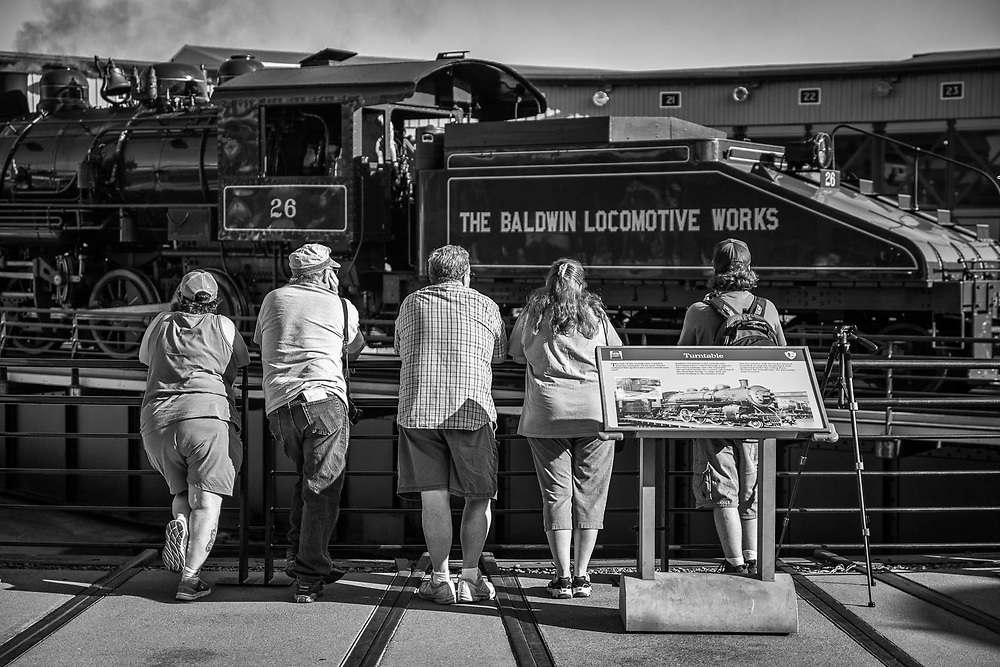 A group of fans take in the sight, sounds and smell of a locomotive awaiting a spin on the turntable at Steamtown.