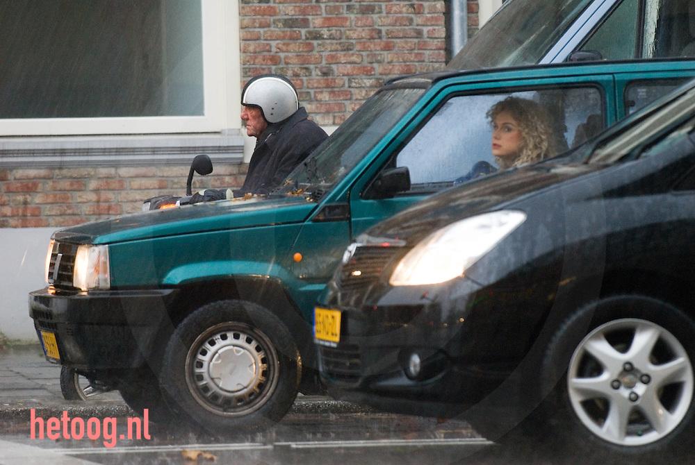 man op brommer wacht voor het verkeerslicht terwijl het hard regent. Vrouw in auto zit droog.