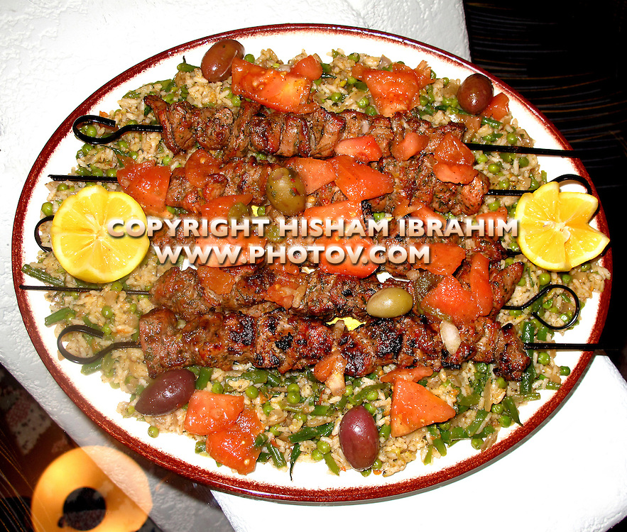 Lamb Kebabs over rice with green peas, olives, tomatoes, and lemon - Middle Eastern Food.