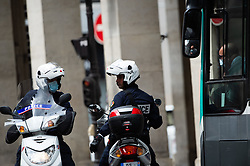 Police forces on scooters wearing facemask speak to a RATP bus driver wearing facemask on Rivoli Street in Paris on May 4, 2020, on the forty-ninth day of a strict lockdown in France, in place to attempt to stop the spread of the new coronavirus (COVID-19). Photo by Raphael Lafargue/ABACAPRESS.COM