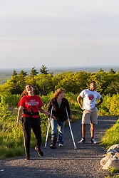 A woman on crutches walks with her teeange son and daughter on an accesible trail near the summit of Mount Agamenticus in York, Maine.