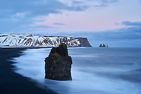 Arnardrangur Sea Stack and Reynisfjara black sand beach after sunset in winter. South coast of Iceland.