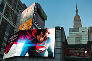 NYC, New York, U.S.  21st May 2013. On a bright large 7th Avenue electric billboard for 'Man of Steel' movie, Superman appears to be looking back to the real Empire State Building, during dusk of a pleasant spring day, with a high of 86ºF/32ºC in Manhattan.