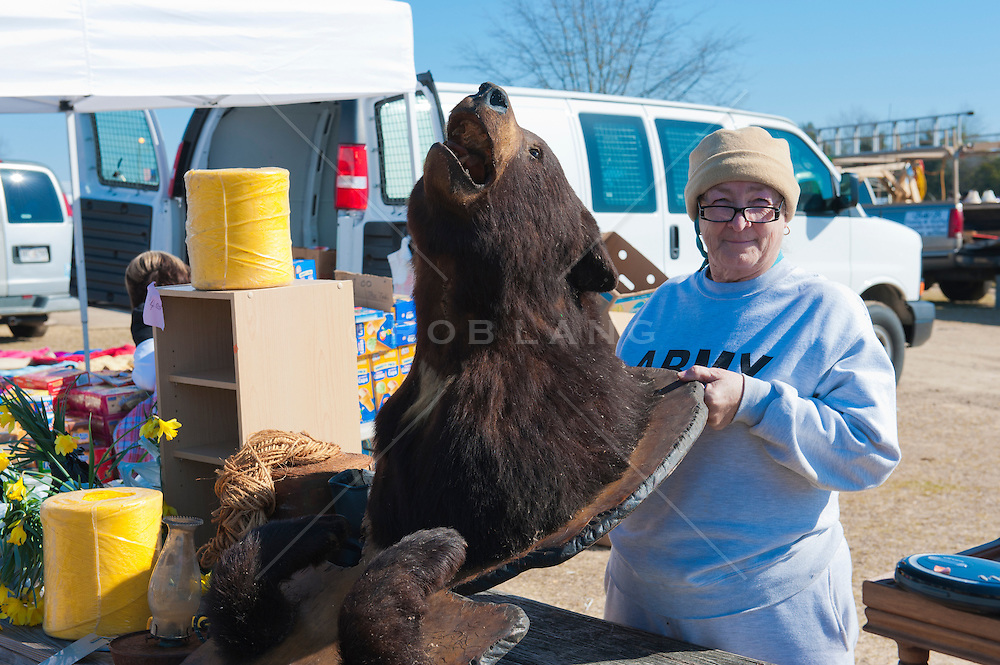 woman in South Carolina holding a stuffed bear at a flea market