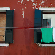 VENICE, ITALY - MARCH 17: An  Italian National Flag composed by three T Shirts and a Japanese flag with a black ribbon hang outside windows on the day of the celebrations for the 150th anniversary of Italy's unification on March 17, 2011 in Venice, Italy. Events in various Italian cities will celebrate the 150th anniversary of Italy's unification until the end of the year. National Festivity begins on March 17.