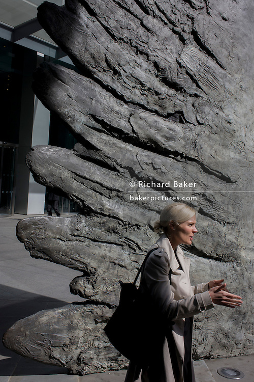 A lady gesticulates with her fingers, echoing the feathered wings of a bronze artwork's wings in the City of London. The ten-metre-tall bronze sculpture is by President of the Royal Academy of Arts, Christopher Le Brun, commissioned by Hammerson in 2009. It is called 'The City Wing' and has been cast by Morris Singer Art Founders, reputedly the oldest fine art foundry in the world.