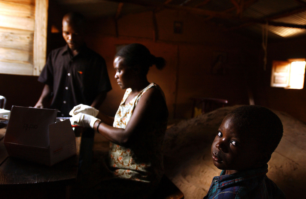 A child waits for results following a test for malaria in a rural health centre in Bie province, Angola
