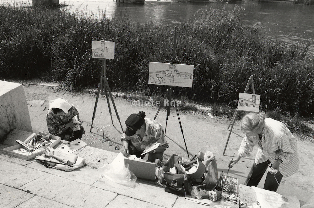 Amateur artists painting by river Italy