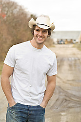 Young man on a dirt road wearing a cowboy hat standing casually with his hands in his pockets