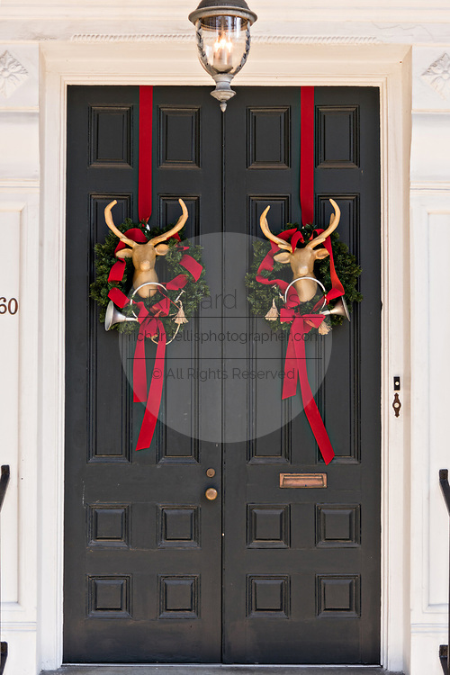 The wooden door of a historic home decorated with Christmas wreaths and deer heads on Meeting Street in Charleston, SC.