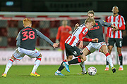 Brentford midfielder Jan Žamburek (31) is tackled by Stoke City midfielder Nick Powell (25) during the The FA Cup match between Brentford and Stoke City at Griffin Park, London, England on 4 January 2020.