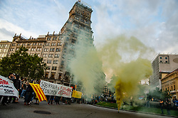 October 1, 2018 - Barcelona, Catalonia, Spain - A yellow smoke flare is seen in front of the protesters with flags and banners..The first actions of surprise on the part of the Committees of Defense of the Republic (CDR) have already taken place at 7:00 a.m. Hundred of people have staged protests and surprises actions through the streets of Barcelona. (Credit Image: © Paco Freire/SOPA Images via ZUMA Wire)