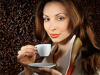 Beautiful young woman holding a cup of coffee with coffee beans background behind her
