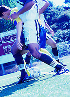 Soccer players fighting for control of the soccer ball at mid field.