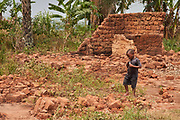 A boy walks near a house that was burnt and destroyed in the village of Lumbambala, Province of Lomami, Democratic Republic of Congo on September 16, 2017. Many of the villagers fled their homes into the bush in March/April 2017 as the Kamwina Nsapu militia battled with security forces in the villages. When CRS visited the village in July, 2017, many of the villagers had still not returned. When they eventually returned, many found their homes had been burnt down. Many of the villagers are living in makeshift shelters while they attempt to rebuild them. To assist these returnees, CRS teams interview each household to determine if it will receive assistance. The ARCC III project has been implemented in four zones, with each household receiving between $5-$25 depending on their vulnerability. The program also involves an awareness component on how to potentially spend the the money with focus on nutrition, education and healthcare. As part of the monitoring and evaluation component, CRS teams return 1 month later to the zone and interview beneficiaries to learn how they have spent the money.