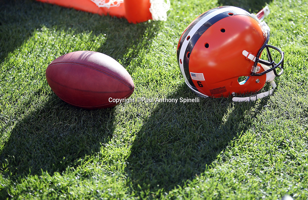 An NFL football and a Cleveland Browns helmet cast long shadows as they lie on the sideline field grass during the Cleveland Browns 2015 week 8 regular season NFL football game against the Arizona Cardinals on Sunday, Nov. 1, 2015 in Cleveland. The Cardinals won the game 34-20. (©Paul Anthony Spinelli)