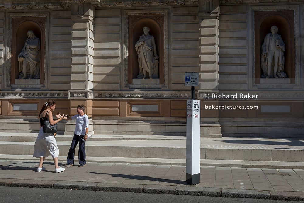 With a further 184 reported UK Covid deaths in the last 24 hrs, a total now of 43,414, old friends greet each other with a hug infront of the statues of Gottfried Leibniz, Georges Cuvier and Carl Linnaeus, and alongside a social distance post outside the Royal Academy on Burlington Gardens, on 26th June 2020, in London, England. Government restrictions have yet to ease when the 2 metre rule is to be realxed on 4th July for 'one metre plus' and when art galleries like the RA re-open. Venues re-opening will be conditional on the progression of the virus and how well social distancing measures are implemented.