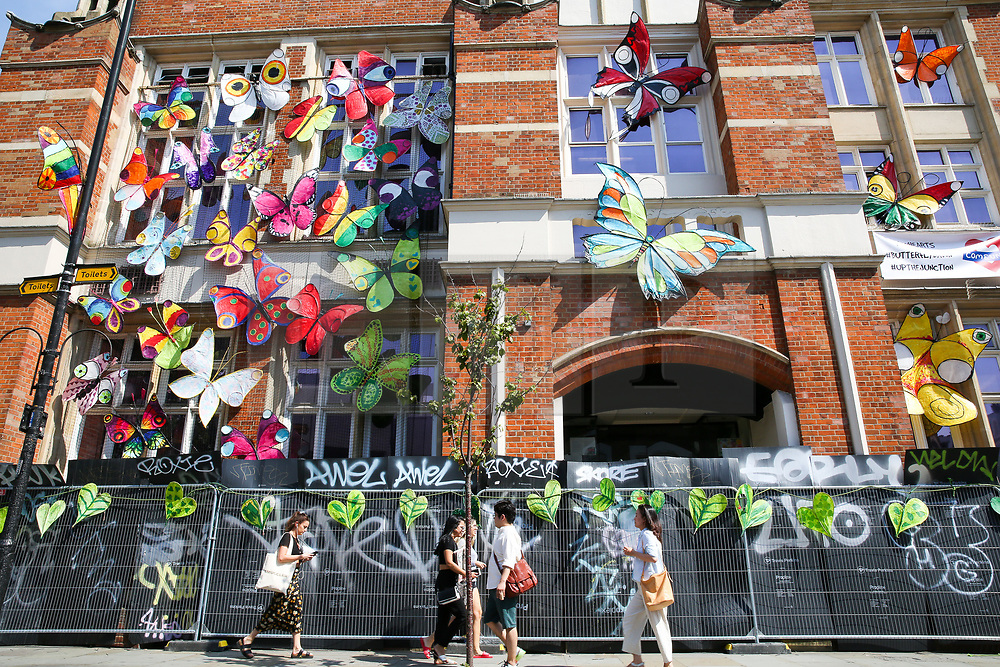 © Licensed to London News Pictures. 24/08/2019. London, UK. People walk past a building covered with colourful butterflies on Ladbroke Grove up ahead of the 2019 Notting Hill Carnival which takes place this weekend and on bank holiday Monday. Up to 1 million people are expected to attend the biggest street party in Europe. Photo credit: Dinendra Haria/LNP