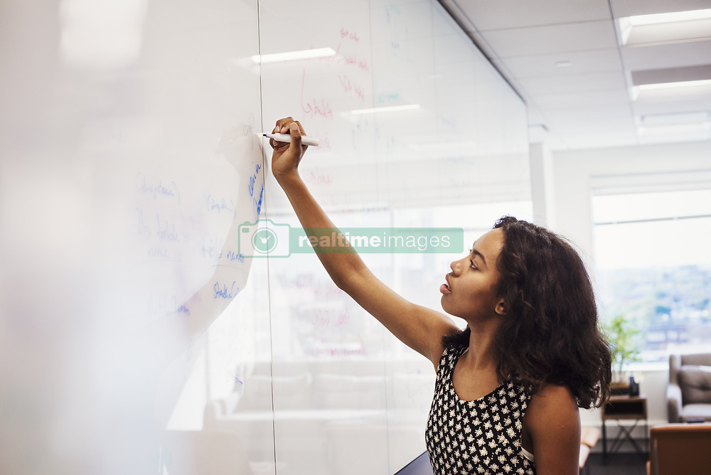 October 23, 2016 - A woman standing in a classroom writing on a whiteboard. (Credit Image: © Mint Images via ZUMA Wire)