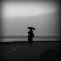A lone woman carrying bags walking in rain along ocean with umbrella.