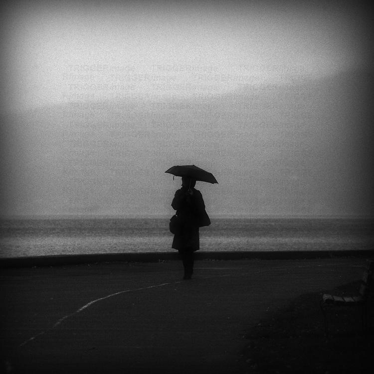 A lone woman carrying bags walking in rain along ocean with umbrella.