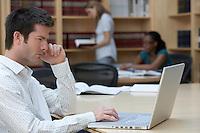 Office worker using laptop in office side view