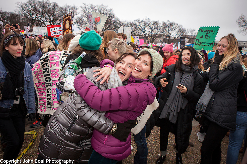 Caryn Mefford, from St. Louis, left, and Mary Holland, of Chicago, embraced as marchers danced and sang in the street to music provided by Sisters of Liberty, on the corner of 7th and Madison, near the National Mall, during the Women's March on Washington where an anticipated 200,000 people turned into an estimated 500,000 to 1 million people, on Saturday, January 21, 2017.  John Boal Photography