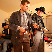 Actors take a break backstage between re-enactments of the infamous gunfight at the OK Corral in Tombstone, Arizona. Tim Fattig (as Frank McLaury) is the actor group leader, pictured here reloading blanks into a gun with Erik Servia (as Doc Holliday) in black hat. Jeremy Caron (as Ike Clanton) is in the background.