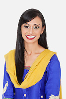 Portrait of pretty Indian woman in traditional wear smiling against gray background