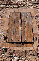 Detail of a shuttered window in a stone building in Chateaurenard, Provence, France.