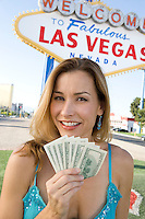 Mid-adult woman holding notes in front of Welcome to Las Vegas sign, portrait
