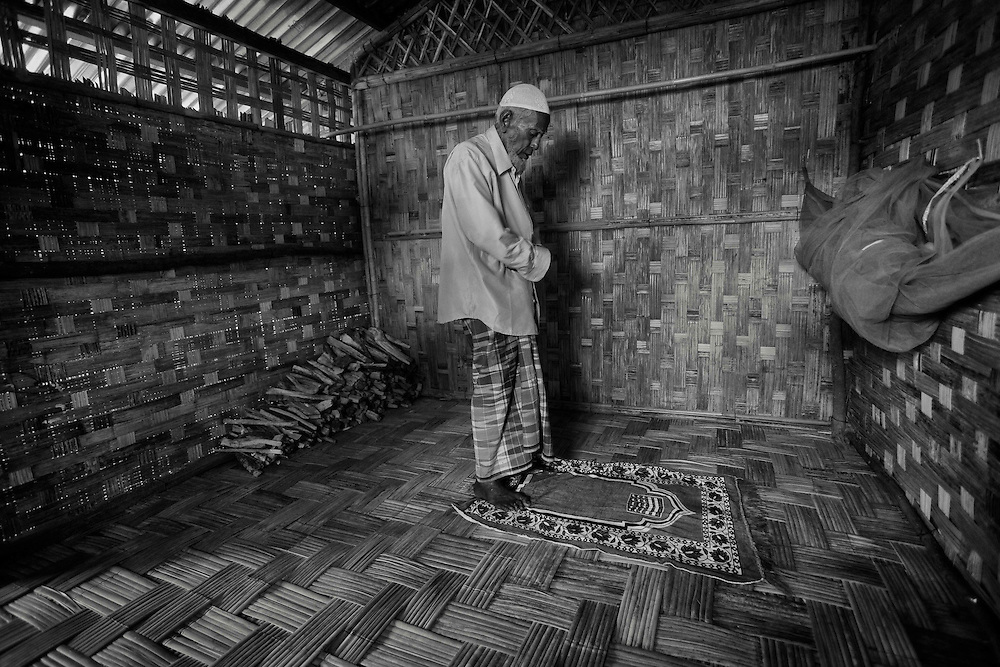 Mohamed Kassim, 84, his wife, Nosimakatton, 25, center and daughter Sobeerakatton, 15, right, look on from their simple bamboo hut inside the Bashara IDP camp on the outskirts of Sittwe, Myanmar, Dec. 17, 2013.  Recent tension in Myanmar have forces thousands of Royhinga Muslims into makeshift camps.