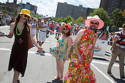 Two men in summer dresses wallk in the parade.