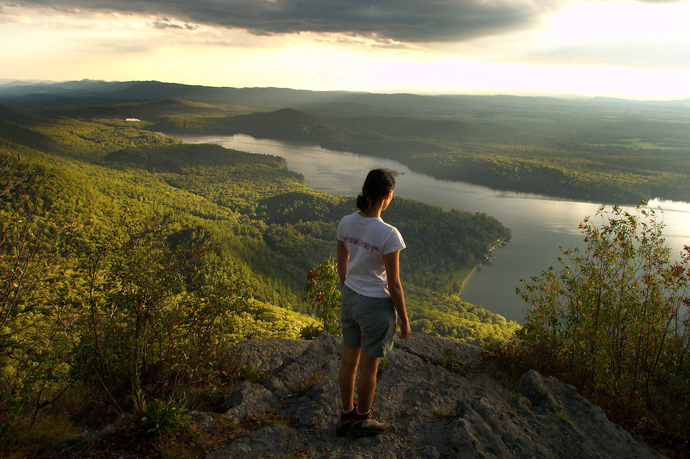 Woman hiker on Rattlesnake Cliffs in the Moosalamoo National Recreation Area looking over Lake Dunmore, Vermont.