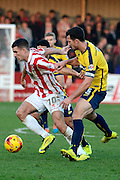 Terry Gornell shields the ball from Jake Wright during the Sky Bet League 2 match between Cheltenham Town and Oxford United at Whaddon Road, Cheltenham, England on 29 November 2014.