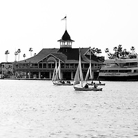 Photo of Balboa Pavilion across Newport Harbor. Balboa Pavilion is a landmark built in 1906 and now houses several businesses including Harborside Restaurant. Newport Beach is a beach community along the Pacific Ocean in Orange County Southern California.