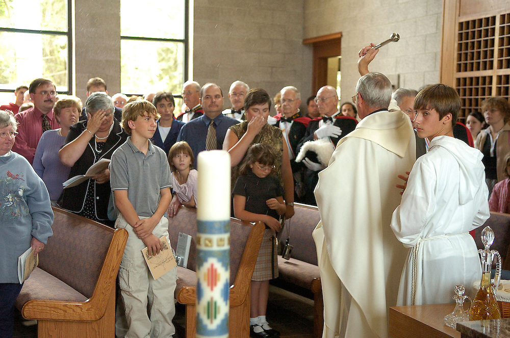 Fr. Joseph Stobba blesses guests with holy water during the dedication of St. Rita Church in Racine. (Photo by Sam Lucero)