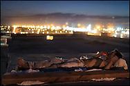 Un migrante fuma un cigarro acostado en el techo del Hotel Migrante, en Mexicali, el 12 de agosto de 2014. En el verano, las temperaturas pueden superar los 40 grados centígrados, por lo que muchos migrantes duermen en la intemperie. El Hotel Migrante, un antiguo hotel en la zona roja fronteriza, ahora convertido en albergue, se encuentra a dos cuadras de la frontera con Calexico, California. (FOTO: Prometeo Lucero)