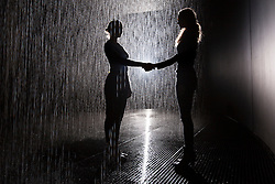 © licensed to London News Pictures. London, UK 03/10/2012. Two women shaking hands in Random International's Rain Room installation, which featuring 100 square metres of pelting water falling from around 4 metre high at The Curve Gallery in Barbican Centre, London. When visitors walk through the rain stops around them. Photo credit: Tolga Akmen/LNP