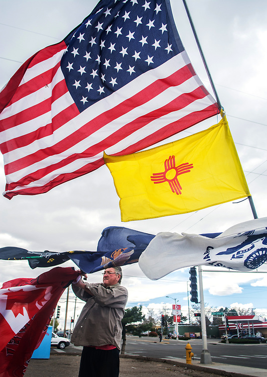 "mkb040417a/metro/Marla Brose --  James the Flag Man, as he called himself, works against the wind to display flags for sale on the corner of Carlisle and Indian School, Tuesday, April 4, 2017, in Albuquerque, N.M. ""It sure is windy,"" said James, who declined to give his last name, but said that Wednesday he'd be at the same place and that the flags would be easier to see. (Marla Brose/Albuquerque Journal)"