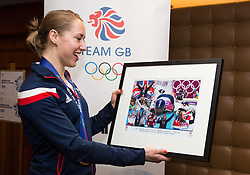 © Licensed to London News Pictures. 25/02/2014. London, UK. Womens skeleton gold medalist, Lizzy Yarnold looks at a framed print of her Olympic achievements at the Sofitel Hotel at Heathrow Airport on 24th February 2014. Photo credit : Vickie Flores/LNP