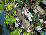 25 SEPTEMBER 2016 - BANGKOK, THAILAND:  Men drink beer and chat in the Pom Mahakan Fort. Forty-four families still live in the Pom Mahakan Fort community. The city of Bangkok has given them provisional permission to stay, but city officials say the permission could be rescinded and the city go ahead with the evictions. The residents of the historic fort have barricaded most of the gates into the fort and are joined every day by community activists from around Bangkok who support their efforts to stay.     PHOTO BY JACK KURTZ