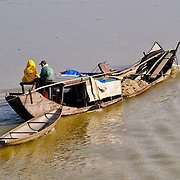 A boat carrying dredged sand makes its way up the Perfume River in Hue, Vietnam, with two people sitting at the stern and towing a smaller wooden canoe.