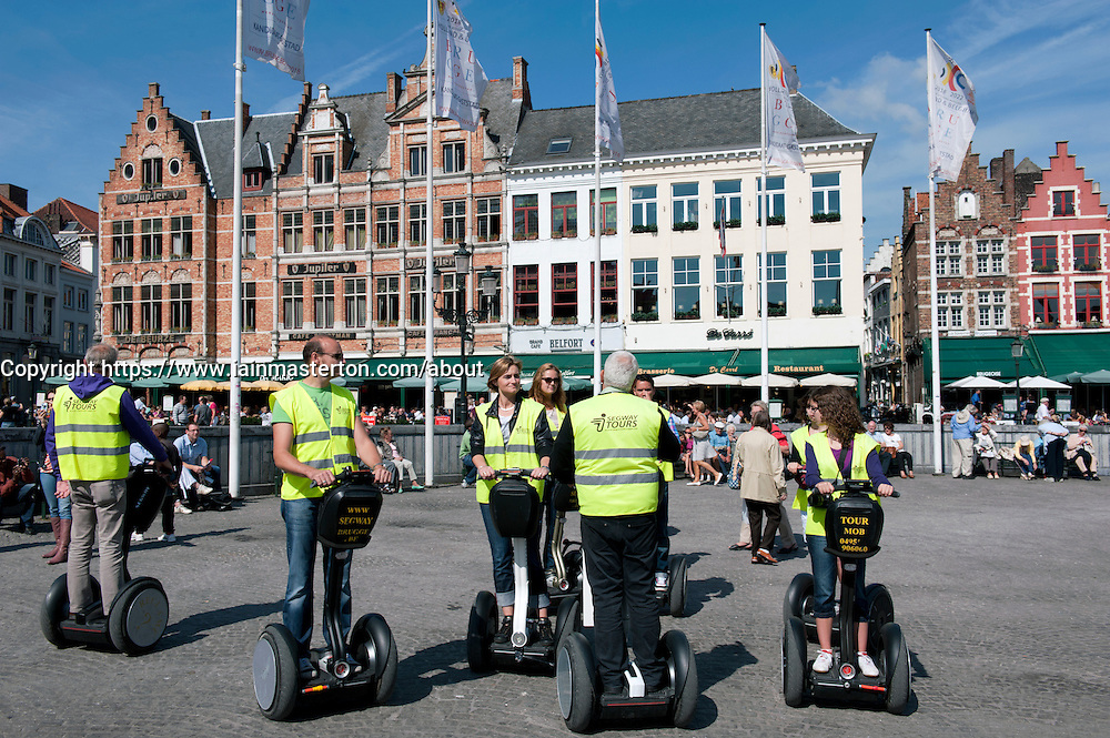 Group of tourists on tour of historic Bruges on Segway electric vehicles in Belgium