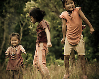 Three little girls play in the grass in the village of Muang Ngoi, Laos, Southeast Asia.