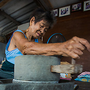 89 year old Kaew grinds sun dried rice to be used in Thai dessert featuring ground rice, coconut, and palm sugar.