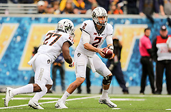 Oct 28, 2017; Morgantown, WV, USA; Oklahoma State Cowboys quarterback Mason Rudolph (2) hands the ball to Oklahoma State Cowboys running back J.D. King (27) during the first quarter against the West Virginia Mountaineers at Milan Puskar Stadium. Mandatory Credit: Ben Queen-USA TODAY Sports