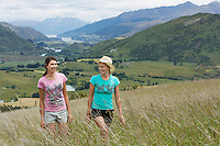 Two women walking in field with hills behind