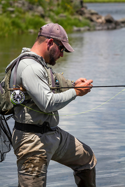 A fly fisherman carefully checks his fly on the Henry's Fork River in Idaho.