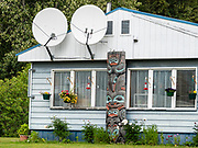 Satellite dishes on a house with a totem pole in Haines, Alaska, USA.